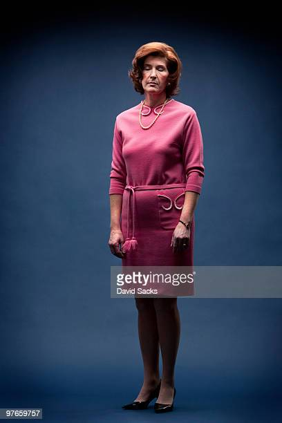 Woman in vintage pink dress with eyes closed