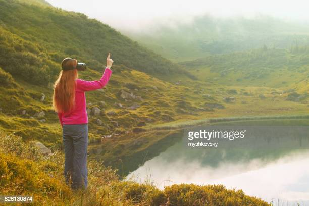 Woman in virtual reality glasses standing near a lake