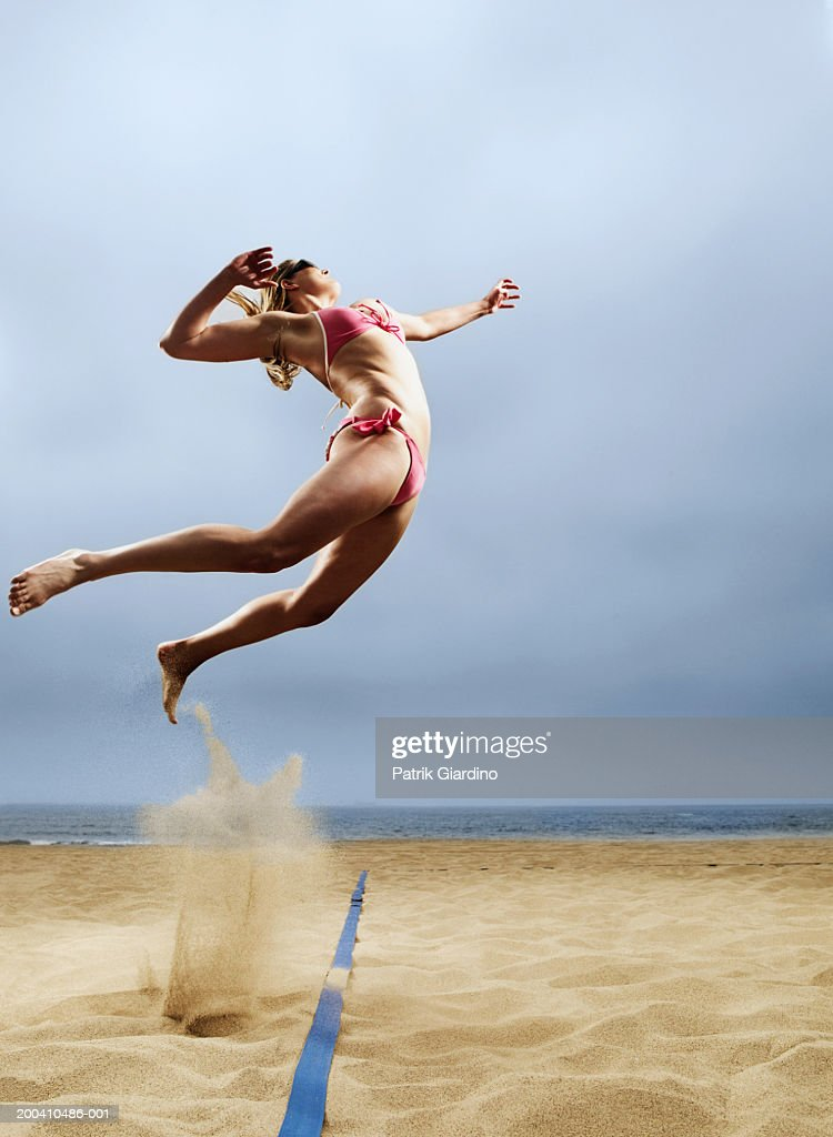 Woman in volleyball spiking postion, side view