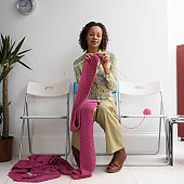 Woman in waiting room, sitting in row of chairs, knitting