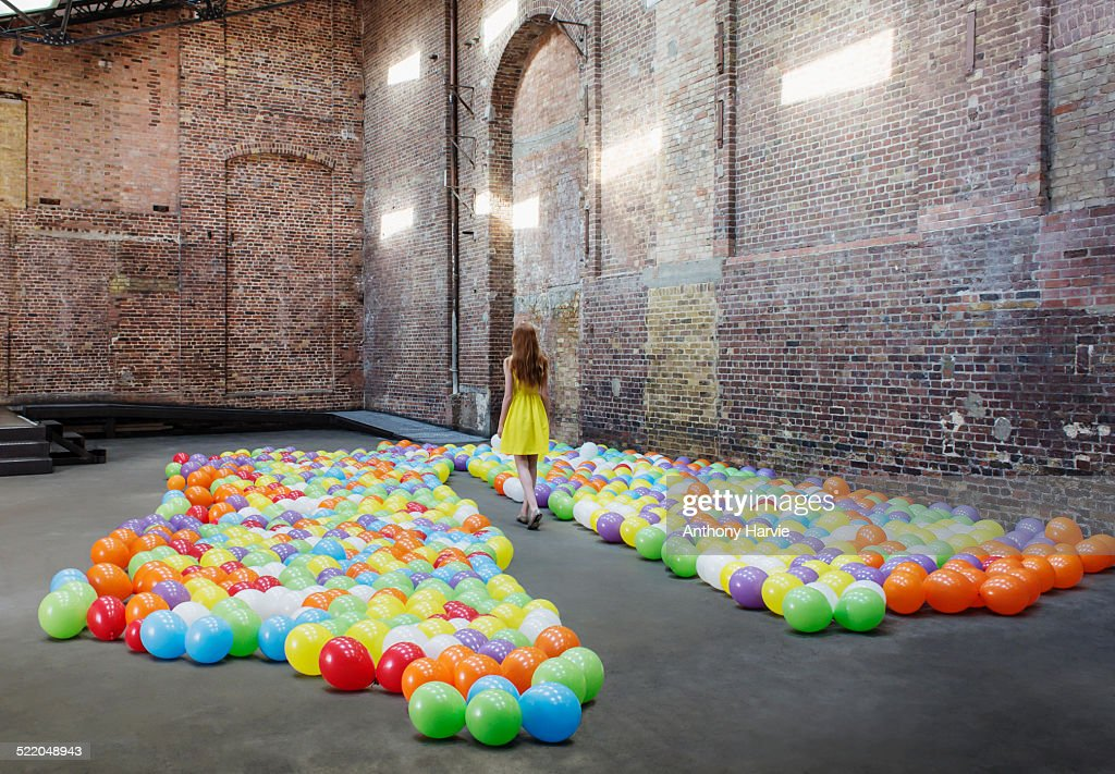 Woman in warehouse with colourful balloons