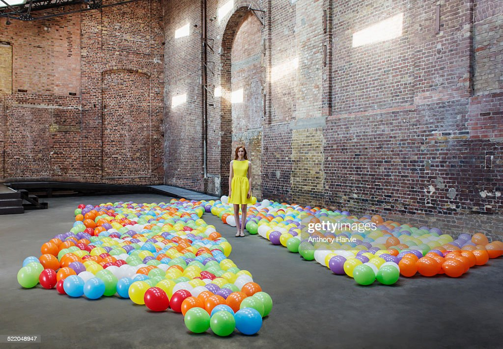 Woman in warehouse with colourful balloons : Stock Photo