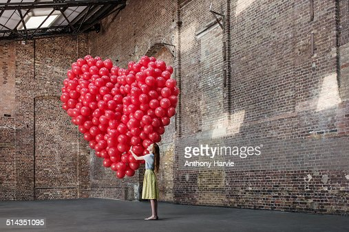 Woman in warehouse with heart made of balloons : Stock Photo