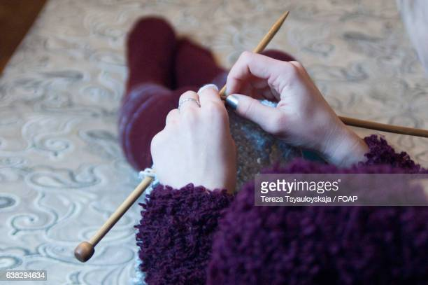 Woman in warm clothing knitting