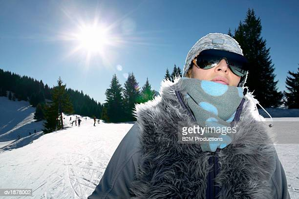 Woman in Warm Skiwear and Ski Goggles on a Sunny Ski Slope