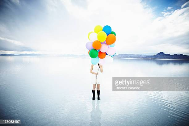 Woman in water standing behind balloons