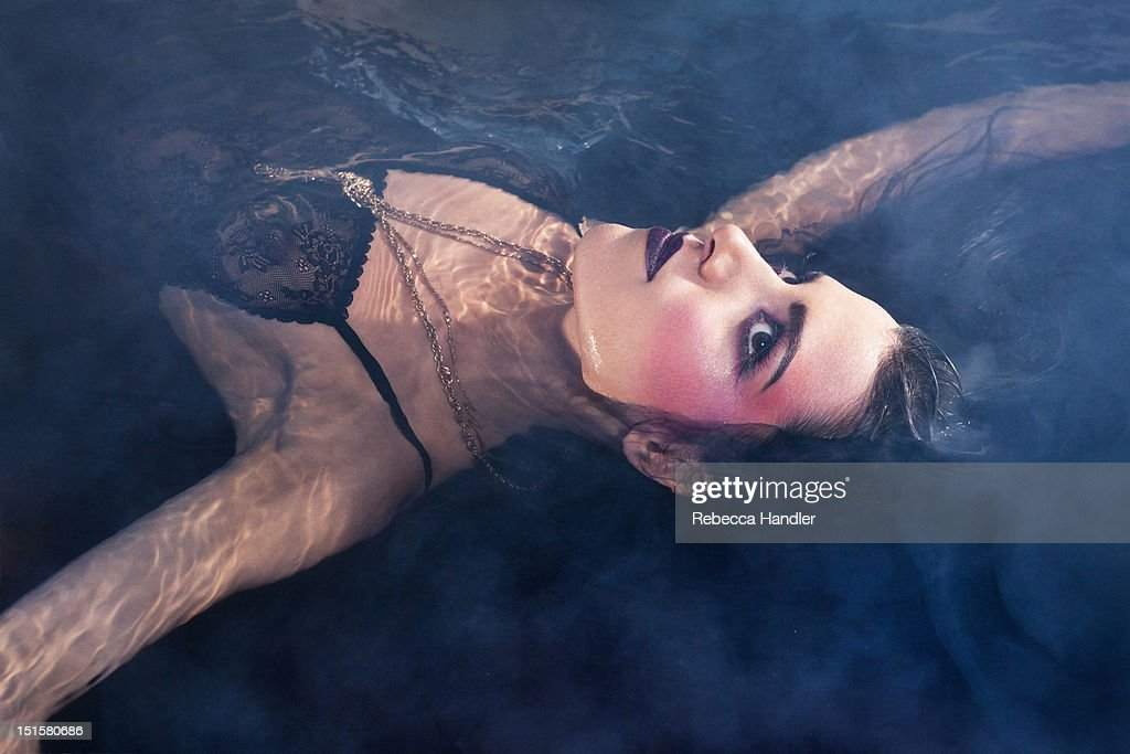 Woman in water with smoke : Stock Photo