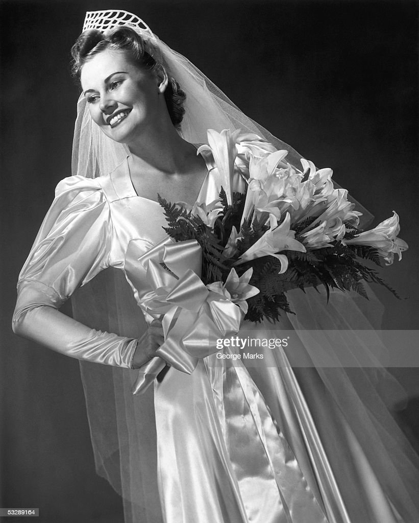 Woman in wedding dress, holding flowers : Stock Photo