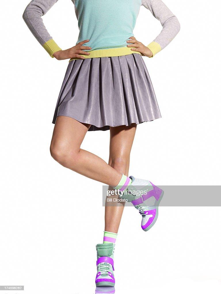 Woman in wedge sneakers with legs crossed
