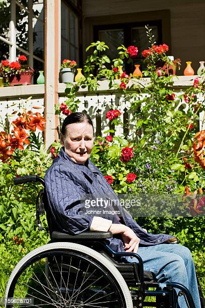Woman in weelchair in fron of a house