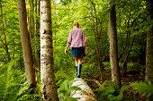 A woman in wellingtons walking along a fallen tree trunk,in woodland.