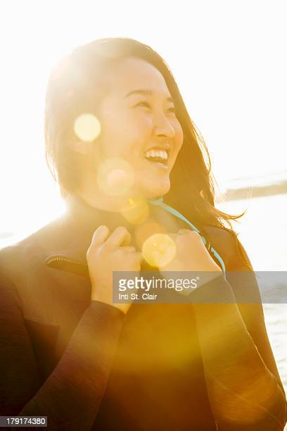 Woman in wetsuit laughing, with sun flare