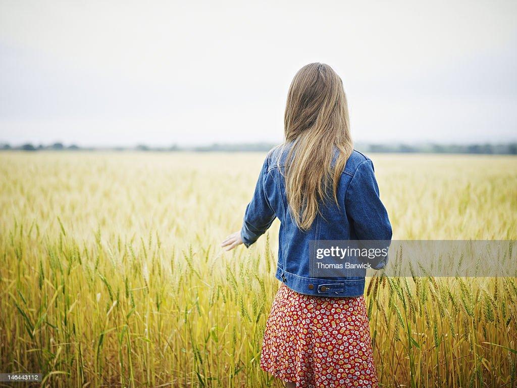 Woman in wheat field hand touching wheat : Stock Photo