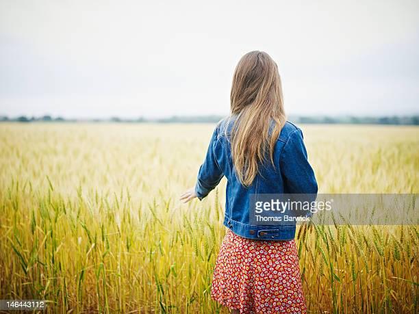 Woman in wheat field hand touching wheat