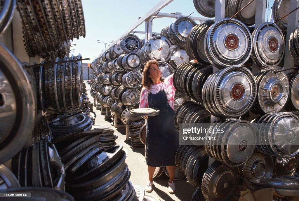 Woman in wheel hub shop, reaching for hub