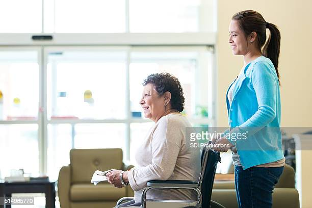 Woman in wheelchair being pushed by granddaughter