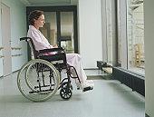 Woman in wheelchair in hospital corridor, side view