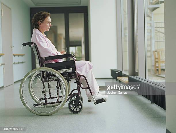 Woman in wheelchair in hospital corridor, side view