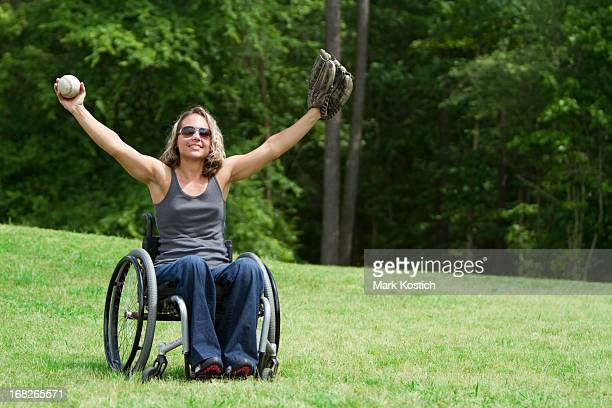 Woman in wheelchair playing catch in a green field
