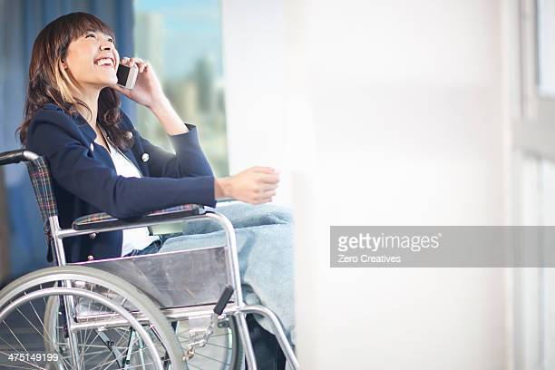 Woman in wheelchair using mobile phone
