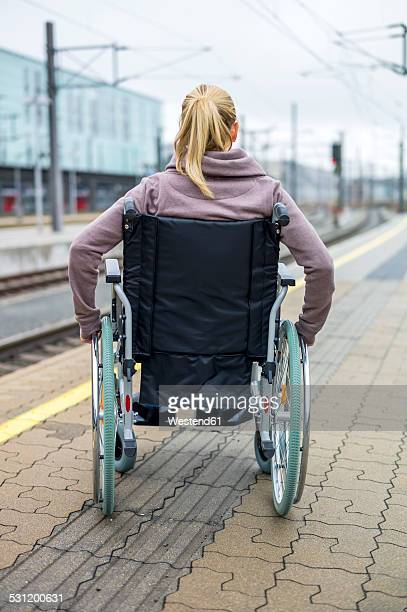 Woman in wheelchair waiting at station platform