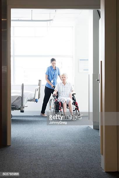Woman in wheelchair with nurse, view through open door