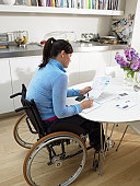 Woman in wheelchair working on accounts at kitchen table