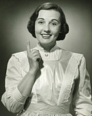 Woman in white apron pointing with finger in studio, (B&W), (Portrait)