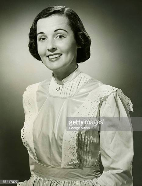 Woman in white apron posing in studio, (B&W), (Portrait)