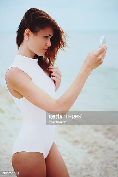 Woman in white bathing suit on sea background