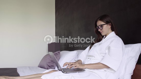 frau im wei en bademantel arbeiten am laptop sitzt auf bett zu hause frauenarbeit auf computer. Black Bedroom Furniture Sets. Home Design Ideas