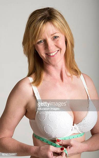 Woman in white bra taking under band measurement