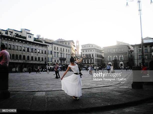 Woman In White Dress Dancing On City Street Against Clear Sky