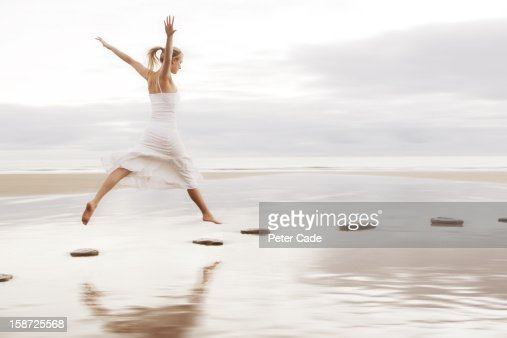 Woman in white dress jumping over stepping stones : Stock Photo
