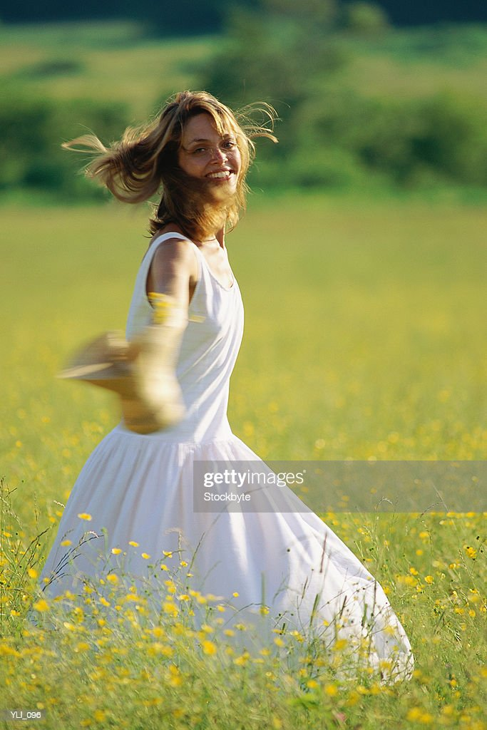 Woman in white dress running across field : Stock Photo