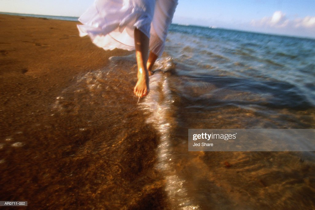 Woman in white dress walking on beach, close-up, low section : Stock Photo