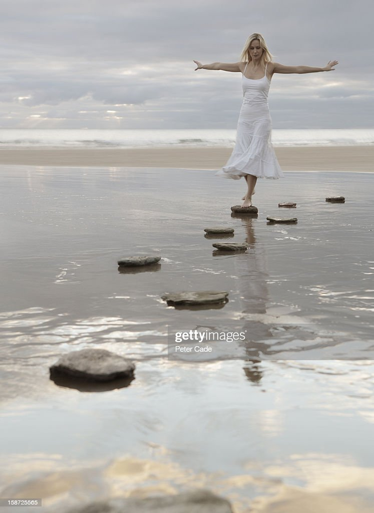 Woman in white dress walking over stepping stones : Stock Photo