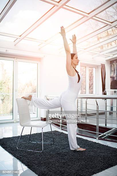 Woman in white exercising yoga
