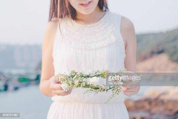 Woman in white holding a fresh floral wreath