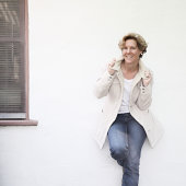 Woman in white jacket standing against white wall