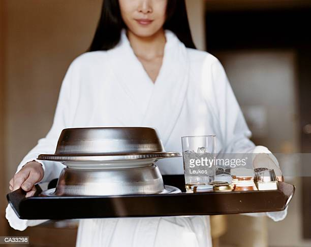 Woman in white robe carrying breakfast tray