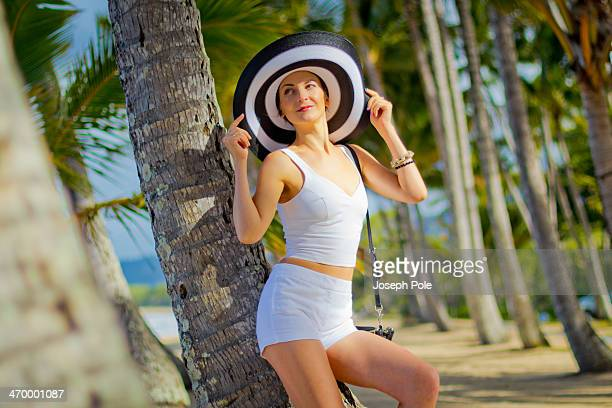 Woman in White Shorts and Large Hat on Palm Beach