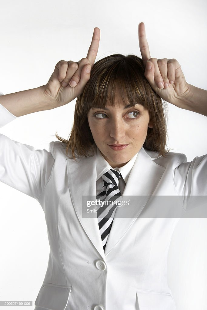 Woman in white suit gesturing devil's horns, close-up : Stock Photo