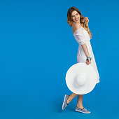 Beautiful young woman in white summer dress, striped sneakers is holding sun hat, looking away over the shoulder and smiling. Full length studio shot on blue background.