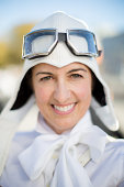 Woman in white wearing pilot hat and goggles