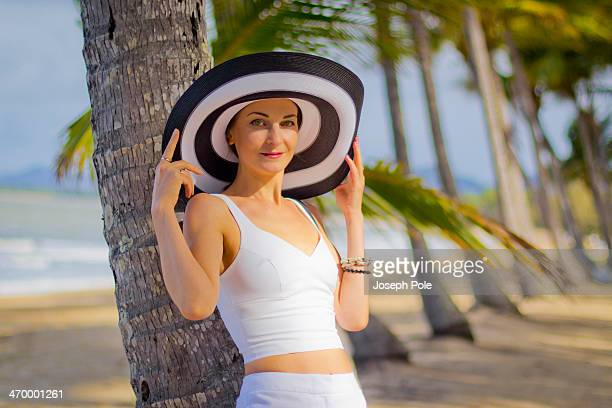 Woman in white with large hat on a tropical beach