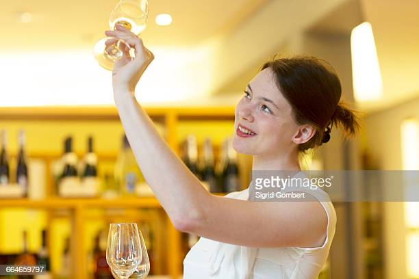 Woman in wine shop holding up wine glass checking cleanliness