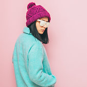 woman in knitted hat and white sunglasses is standing with her back. pastel fashion clothing.