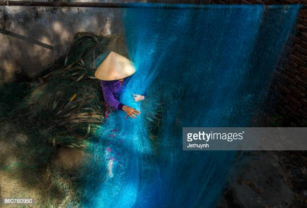 Woman in with conial hat mending fishing net