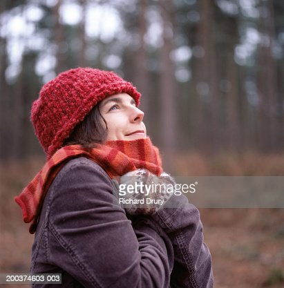 Woman in woods with arms folded over chest, looking upwards : Stock Photo
